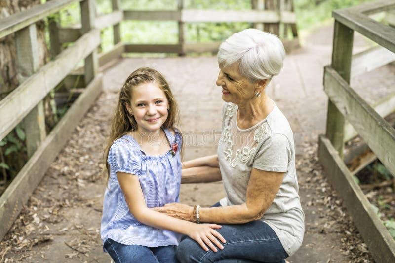 De grootmoeder en de kleindochter brengen het weekend in het park door stock fotografie