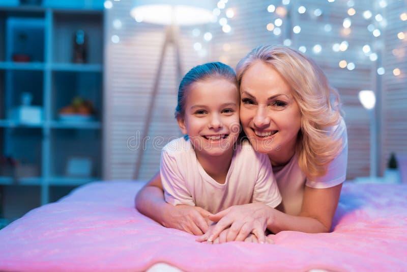 De grootmoeder en de kleindochter koesteren thuis bij nacht stock foto's