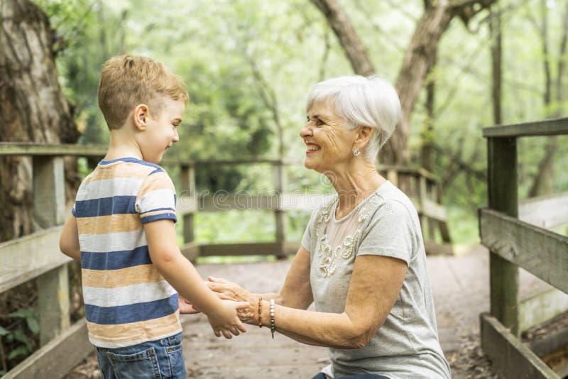 De grootmoeder en de kleinzoon brengen het weekend in het park door stock afbeelding