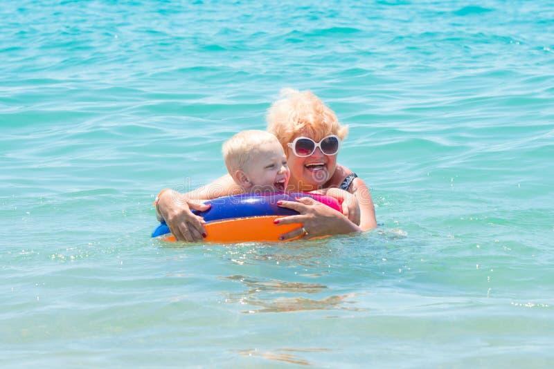De grootmoeder en weinig kleinzoon zwemmen in het overzees De baby in de bouncy multicolored cirkel De vakantie van de zomer stock afbeelding