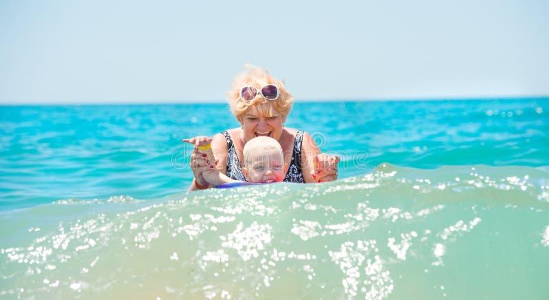 De grootmoeder en weinig kleinzoon zwemmen in het overzees De baby in de bouncy multicolored cirkel De vakantie van de zomer stock foto