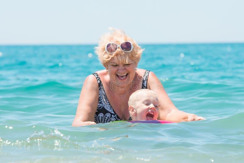 De grootmoeder en weinig kleinzoon zwemmen in het overzees De baby in de bouncy multicolored cirkel De vakantie van de zomer stock fotografie