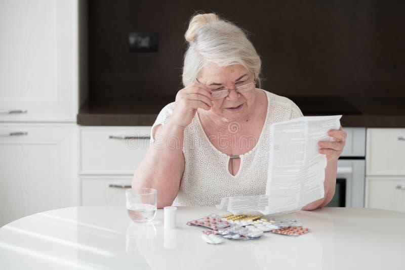 De grootmoeder in glazen leest de instructie op toepassing van geneesmiddelen stock fotografie