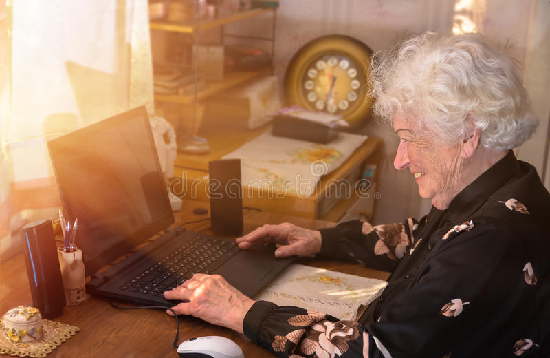 De grootmoeder leert om thuis aan de computer te werken royalty-vrije stock afbeeldingen