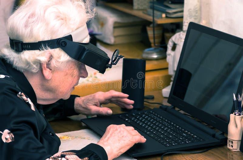 De grootmoeder leert om thuis aan de computer te werken stock foto