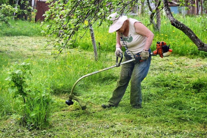 De grootmoeder maait het gras royalty-vrije stock afbeeldingen