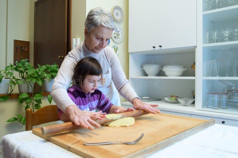De grootmoeder onderwijst haar kleinkinderen hoe te om deegwaren te maken royalty-vrije stock afbeeldingen