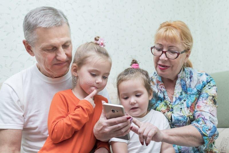 De grootmoeder toont smartphone aan haar kleindochters royalty-vrije stock fotografie