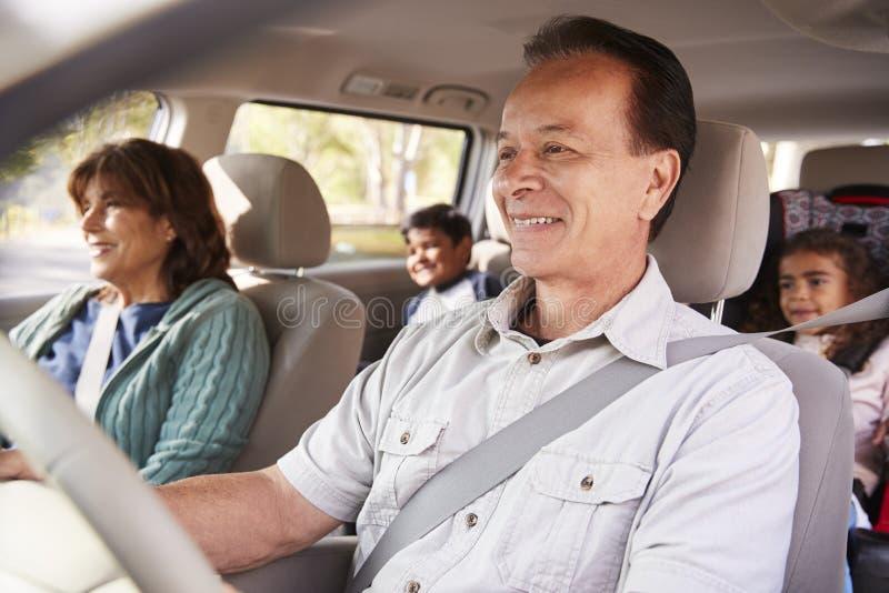 De grootouders met kleinkinderen in een auto op een weg halen over royalty-vrije stock fotografie