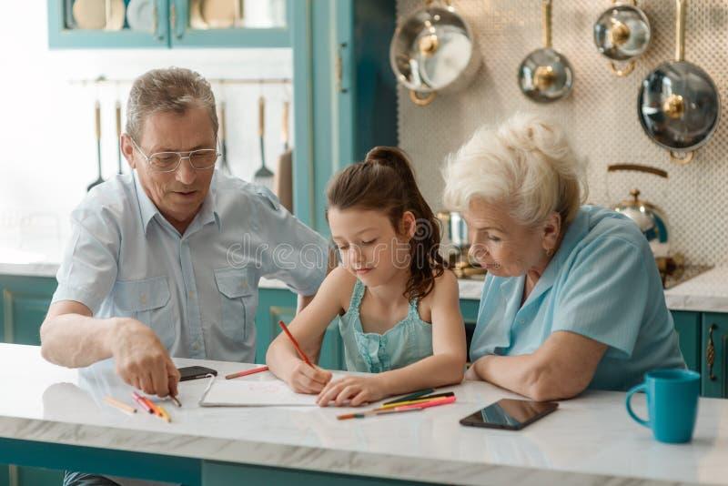 De grootouders onderwijzen een jong geitje stock afbeelding