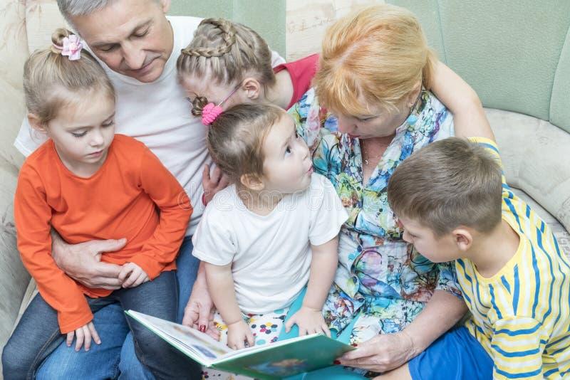 De grootouders onderwijzen kleinkinderen om te lezen stock afbeeldingen