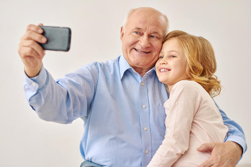 De grootvader en de kleindochter maken selfie stock foto's