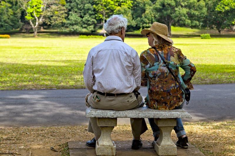 De grootvader en de grootmoeder zitten op bank in Botanische tuin stock foto's