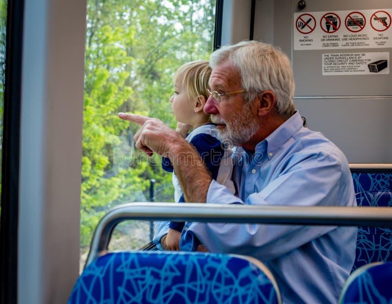 De grootvader en de Kleinzoon brengen samen Tijd aan Trein door royalty-vrije stock fotografie