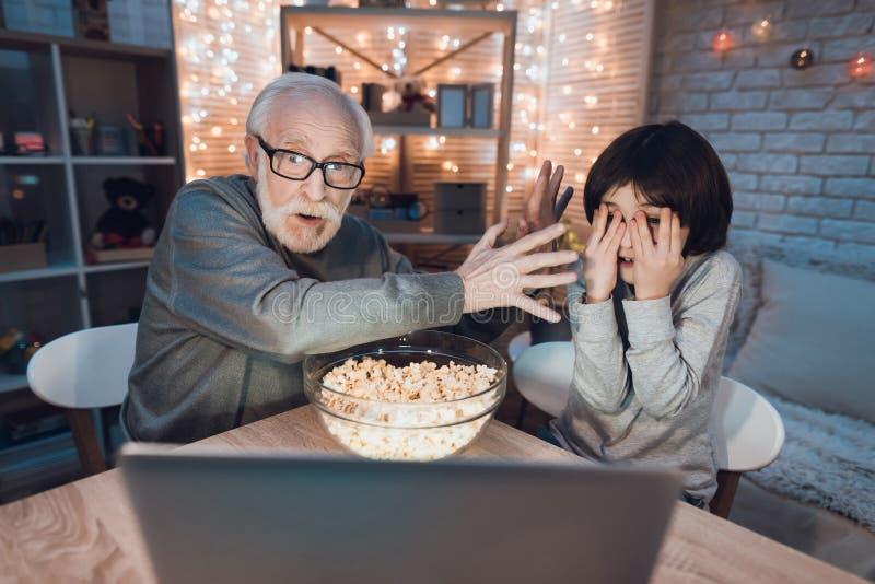 De grootvader en de kleinzoon letten thuis op enge film bij nacht stock foto's