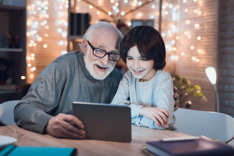 De grootvader en de kleinzoon letten thuis op interessante film bij nacht stock afbeelding