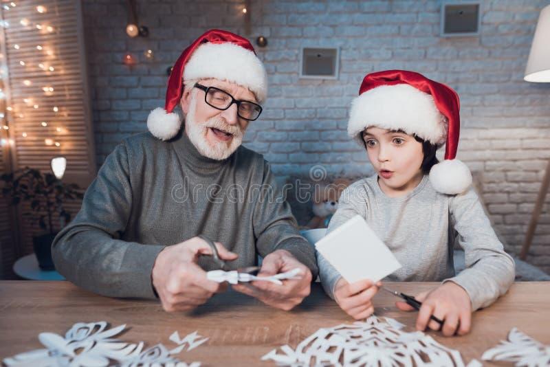 De grootvader en de kleinzoon maken thuis Kerstmisdecoratie bij nacht stock afbeeldingen