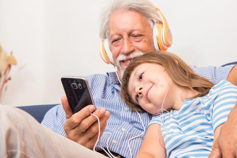 De grootvader en de kleinzoon met hoofdtelefoons luisteren aan muziek het koesteren stock fotografie