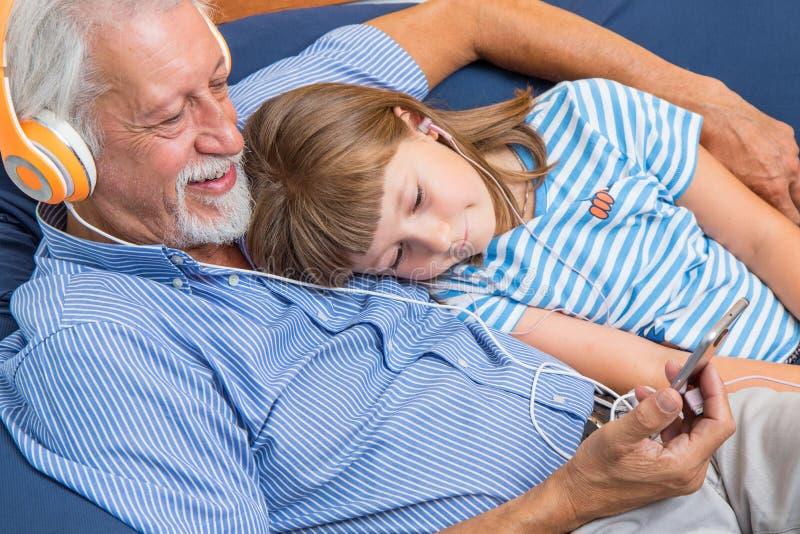 De grootvader en de kleinzoon met hoofdtelefoons luisteren aan muziek het koesteren royalty-vrije stock afbeeldingen