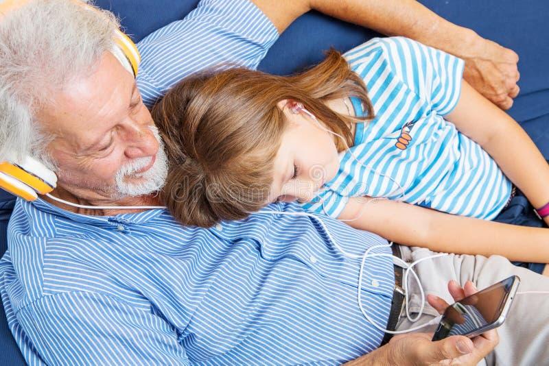 De grootvader en de kleinzoon met hoofdtelefoons luisteren aan muziek het koesteren royalty-vrije stock fotografie