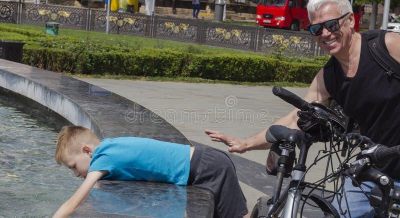 De grootvader en de kleinzoon op een verbinding lopen in het Park dichtbij de fontein stock fotografie