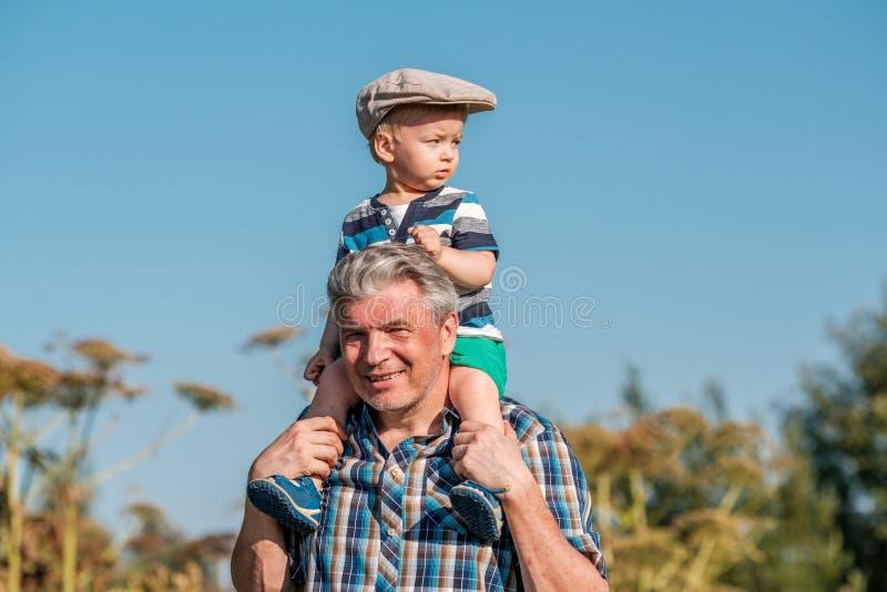 De grootvader vervoert de jongen van de kleinzoonpeuter op zijn schouders royalty-vrije stock afbeeldingen
