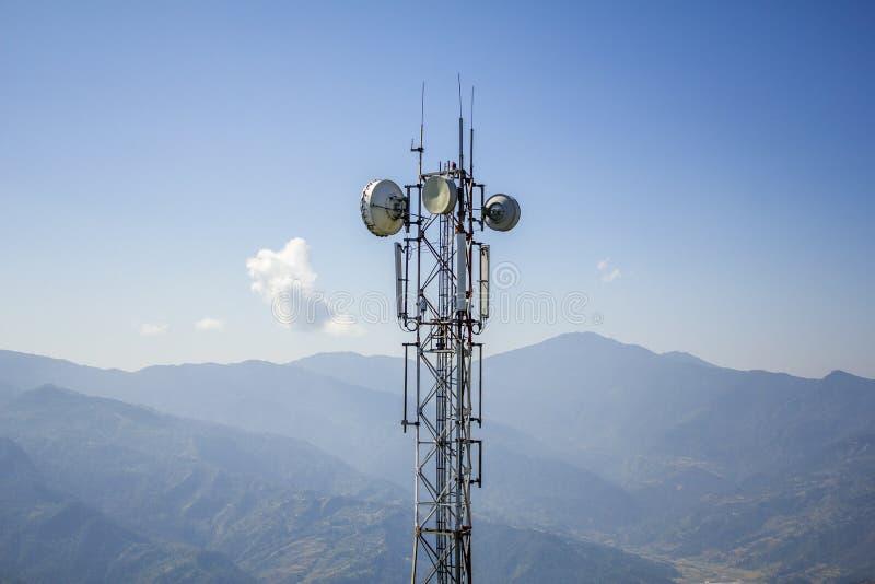 De grote antenne van de metaaltoren met satellietschotels tegen de achtergrond van bergen en blauwe hemel stock afbeelding