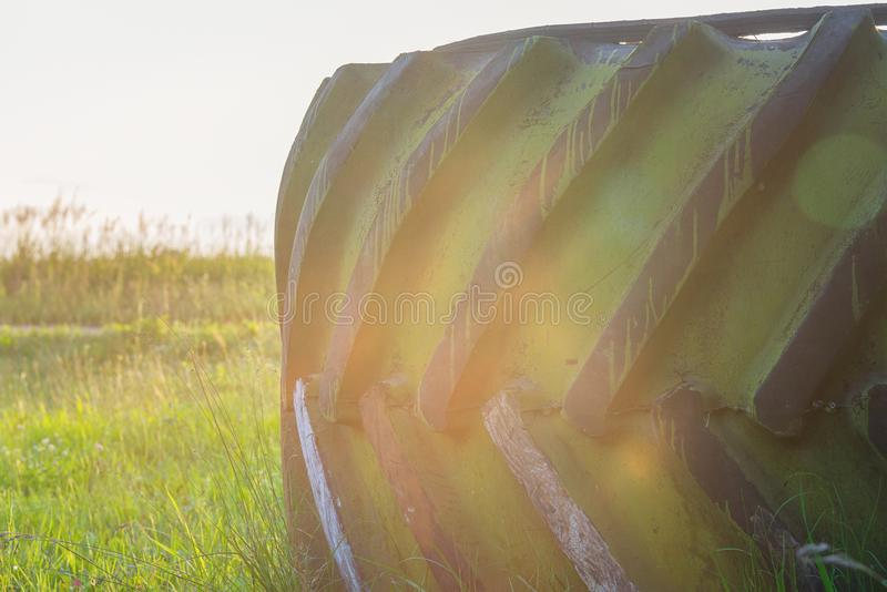 De grote band van het vrachtwagenwiel op het gras onder grijze hemel met lensgloed royalty-vrije stock foto