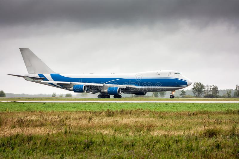 De grote bewegingen van het ladingsvliegtuig op de belangrijkste taxibaan in zware regen royalty-vrije stock afbeelding