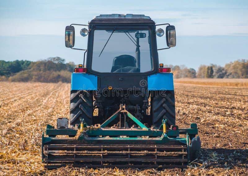 De grote blauwe tractor ploegt het gebied en verwijdert de overblijfselen van eerder gemaaid graan royalty-vrije stock afbeelding