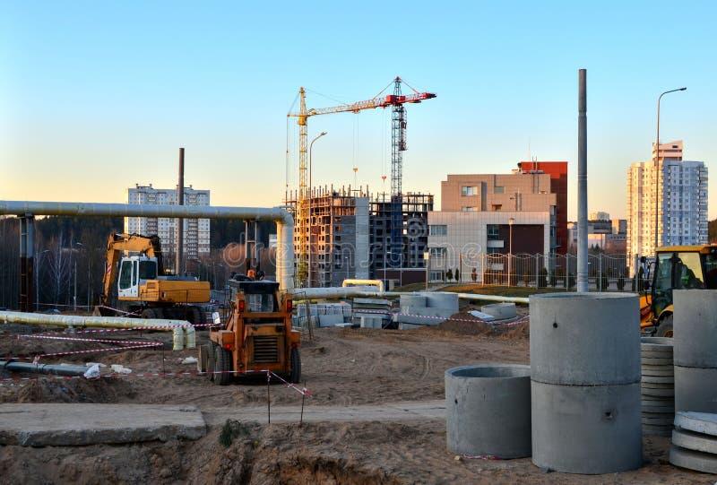 De grote bouwwerf met werkende kranen en zware machines voor weg werkt, wiellader, bulldozer, graafwerktuig stock afbeeldingen
