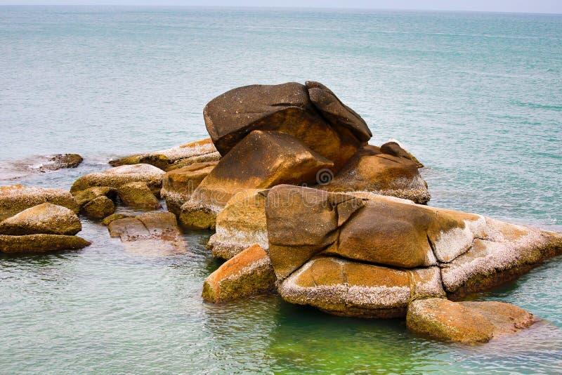 De grote bruine beige steenstapel doorstond ongelijk in het oceaan groene transparante water achtergrondsteenstrand stock afbeeldingen