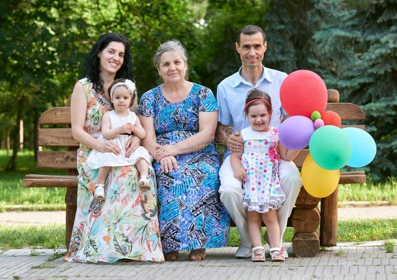 De grote familie zit op houten bank in stadspark, zomer, kind, ouder en grootmoeder, kleine groep van vijf mensen met ballon royalty-vrije stock foto's