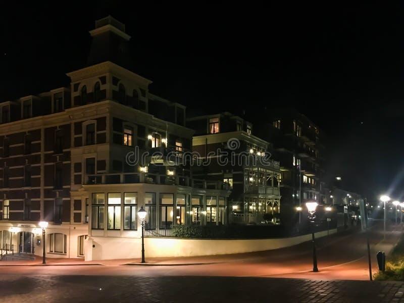 De grote flats complexe bouw met de weg van de stadsstraat en aangestoken lantaarnpalen in de populaire stad Scheveningen Nederla stock foto