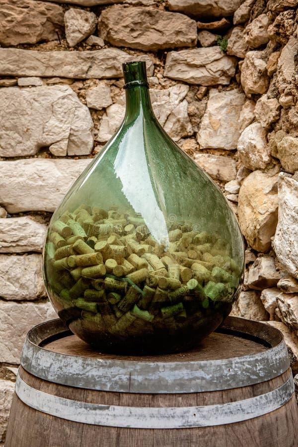 De grote fles van de glaswijn half volledig van kurkt in schilderachtige Eze royalty-vrije stock fotografie