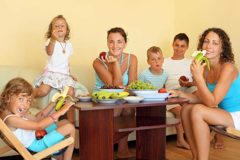 De grote gelukkige familie eet fruit in comfortabele ruimte stock foto