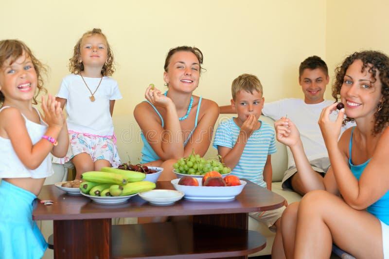 De grote gelukkige familie met kinderen eet fruit royalty-vrije stock foto