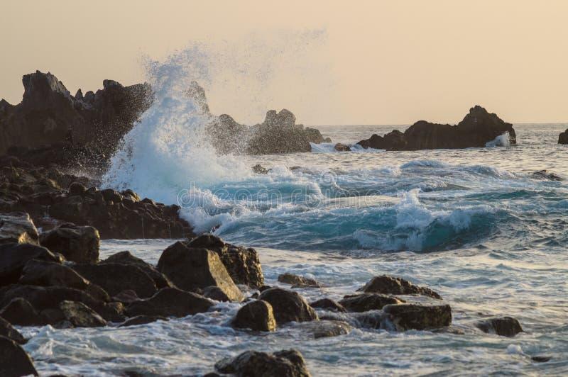 De grote golven met ploetert het breken op de kust bij zonsondergang stock fotografie