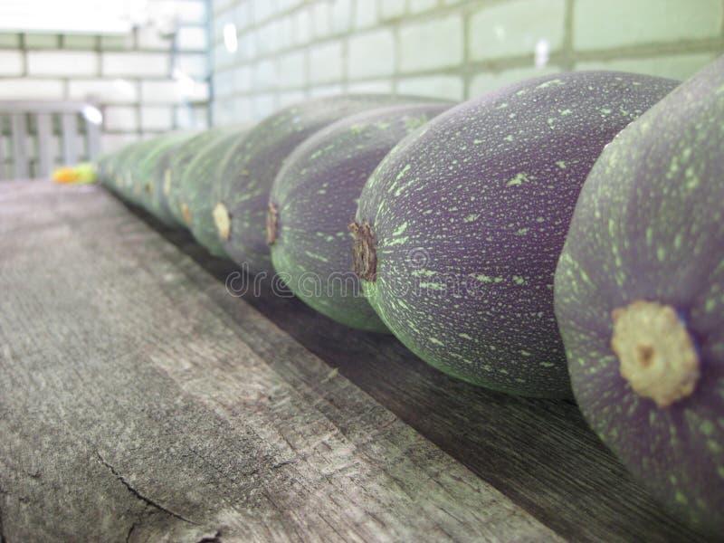 De grote groene courgette ligt op een rij op een eiken lijst stock foto