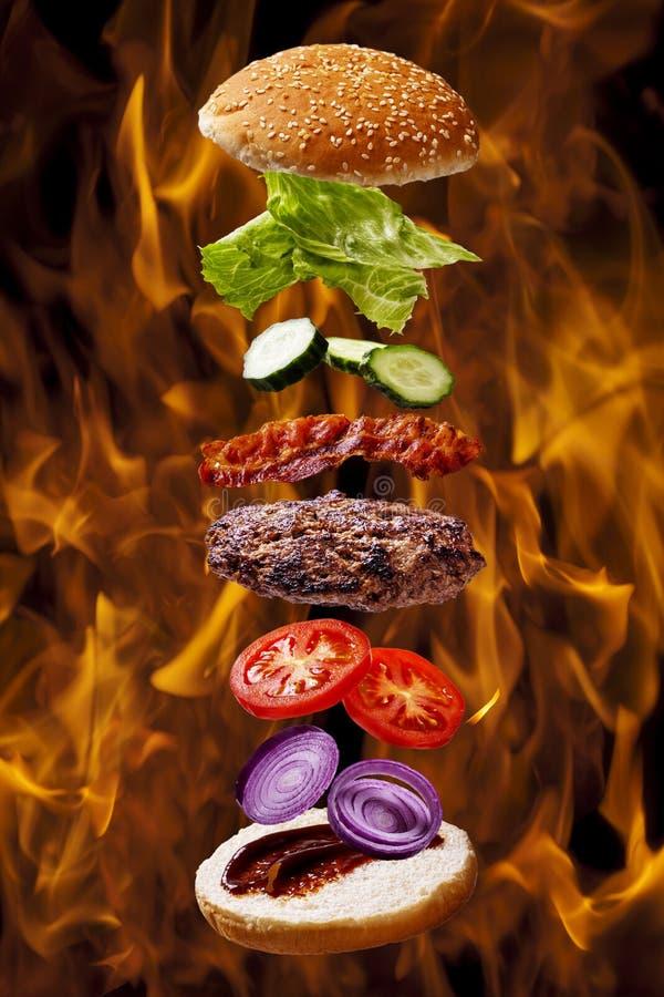De grote hamburger van de baconbarbecue bij de grill van de brandvlam royalty-vrije stock fotografie