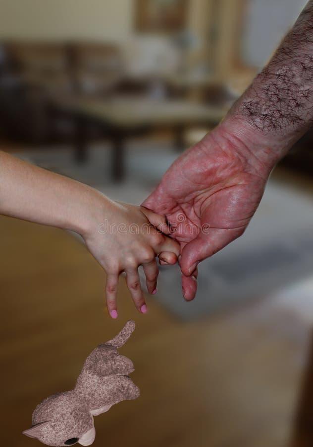 De grote, harige man hand trekt de hand van het kleine meisje stock afbeelding