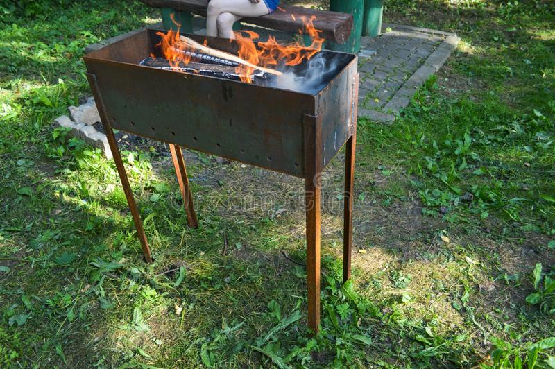 De grote het metaalkoperslager van het ijzergietijzer voor de picknickkebabs van de grillbarbecue met het houten branden opent ee stock afbeeldingen