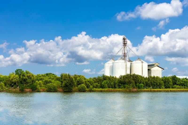 De grote industriële fabriek en silobouw bij zijkust van overzees met blauwe hemel en wolk in heldere dag royalty-vrije stock fotografie