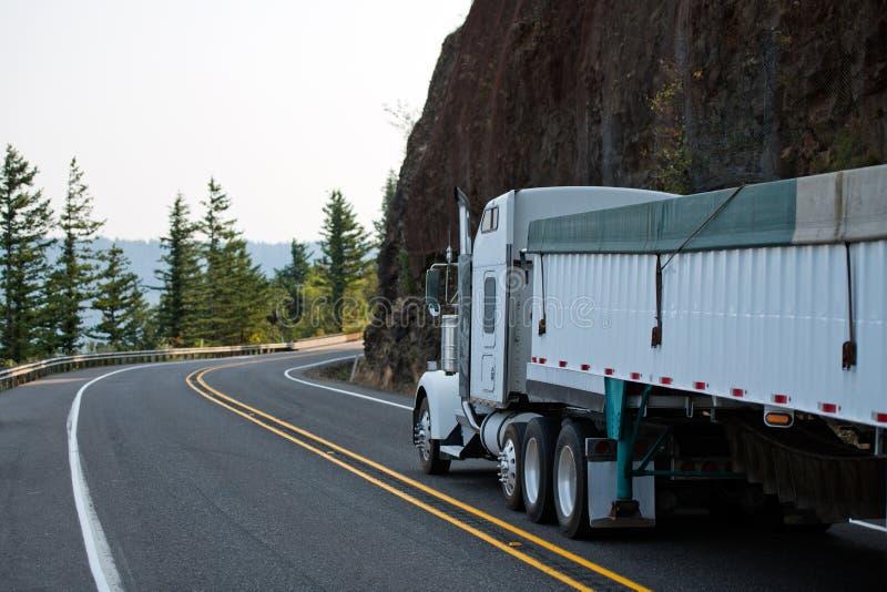 De grote installatie witte semi vrachtwagen met massa behandelde het semi aanhangwagen lopen royalty-vrije stock foto's
