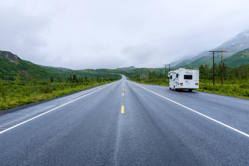 De grote kampeerauto parkeerde aan een kant van een weg in Alaska royalty-vrije stock afbeeldingen