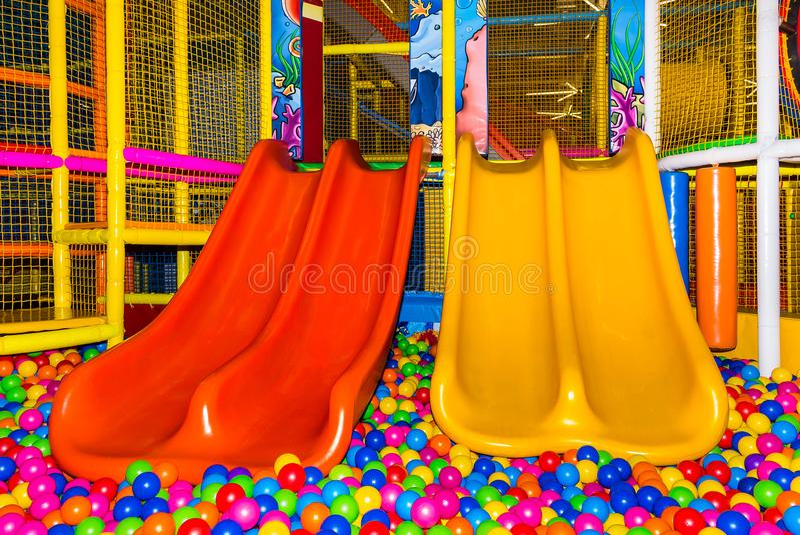 De grote kinderen` s speelkamer met een dia en de kleurrijke ballen in vermaak centreren stock foto's