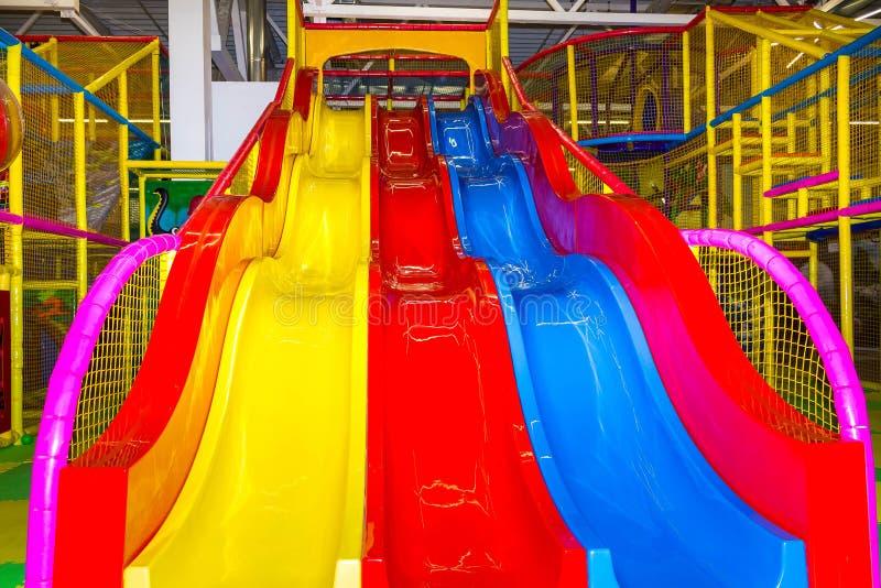 De grote kinderen` s speelkamer met een dia en de kleurrijke ballen in vermaak centreren stock afbeelding