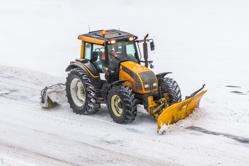 De grote machine van de sneeuw ploegende tractor op het werk aangaande de weg tijdens een sneeuwonweer in de winter stock afbeelding