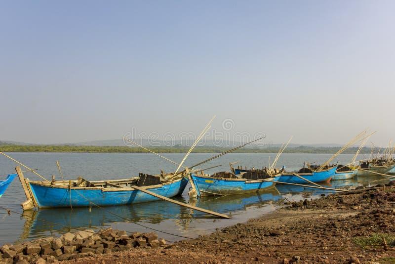 De grote oude blauwe houten vissersboten bonden met kabels aan de kust tegen de achtergrond van de rivier en het groene bos royalty-vrije stock afbeeldingen