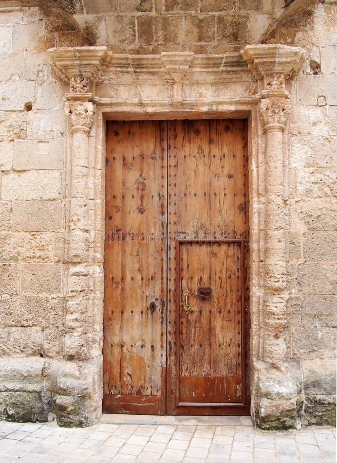De grote oude bruine houten die deur met geroest die ijzer wordt behandeld beslaat sleutelgat en handvat in een overladen gesnede stock foto